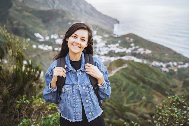 Glückliche lächelnde frau mit rucksack auf dem ozean und den bergen. reise- und lifestyle-konzept