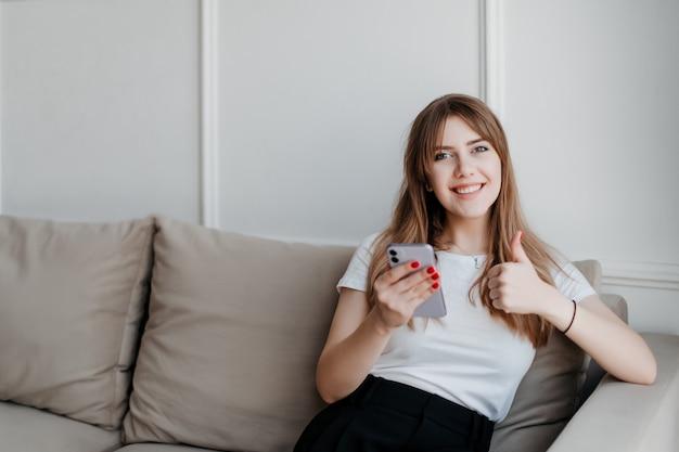 Glückliche lächelnde frau mit telefon, das daumen oben auf einer couch zu hause in der hellen modernen wohnung sitzend zeigt