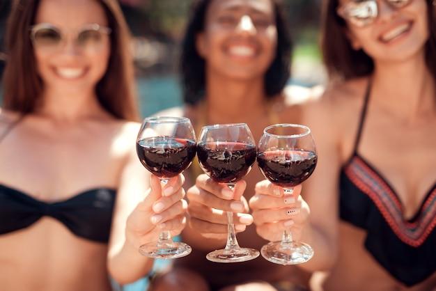 Glückliche lächelnde frauen, die wein am poolside trinken
