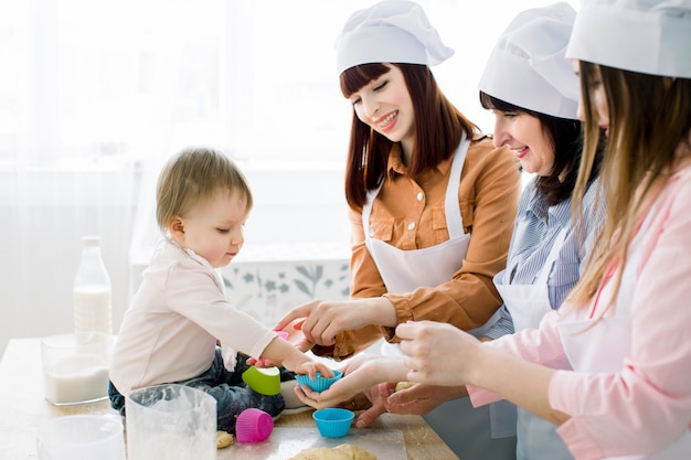 Glückliche lächelnde frauen, die zusammen mit dem kleinen baby zu hause küche, muttertag, familienkonzept backen. frauen geben teig in farbige silikon-backbecher für muffins