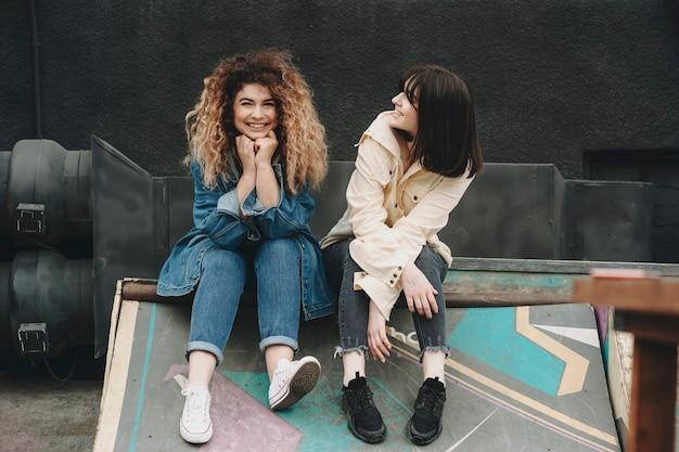 Glückliche lächelnde frauen in der sommer-freizeitkleidung, die zusammen auf holzbrettern auf altem verlassenem industrie sitzt