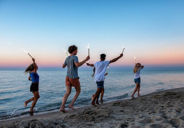 Glückliche lächelnde freunde, die am strand mit funkelnden kerzen in der hand laufen