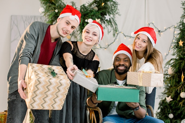 Glückliche lächelnde freunde, die geschenkboxen halten und spaß an der weihnachtsfeier haben
