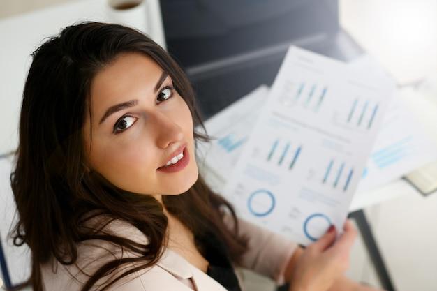 Glückliche lächelnde geschäftsfrau halten papiere in der hand mit grafik