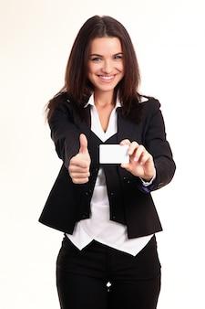 Glückliche lächelnde geschäftsfrau mit den daumen herauf geste und in der hand eine visitenkarte