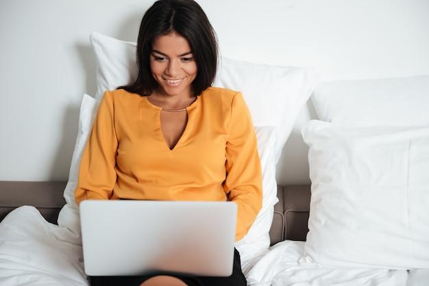 Glückliche lächelnde geschäftsfrau mit laptop, der im bett liegt