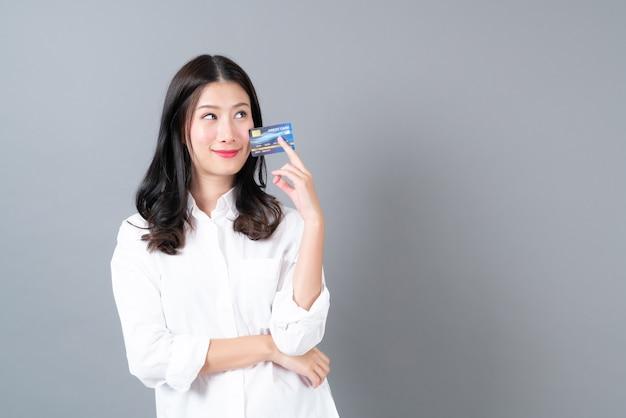 Glückliche lächelnde geschenkkreditkarte der jungen asiatischen frau in der hand auf grauem hintergrund