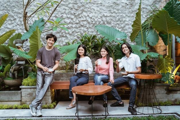 Glückliche lächelnde gruppe von freunden, die gartenparty im freien mit kaffeegetränken haben