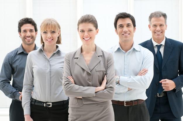 Glückliche lächelnde gruppe von geschäftsleuten, die zusammen im büro stehen