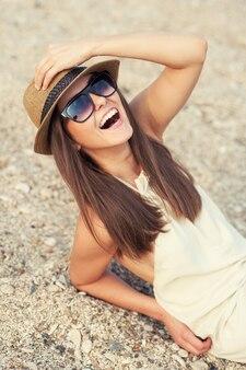 Glückliche lächelnde hipsterfrau im hut am strand