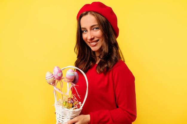 Glückliche lächelnde hübsche frau mit dem lockigen haar, das roten pullover und rote baskenmütze trägt, die mit osterkorb über isolierter gelber wand aufwirft