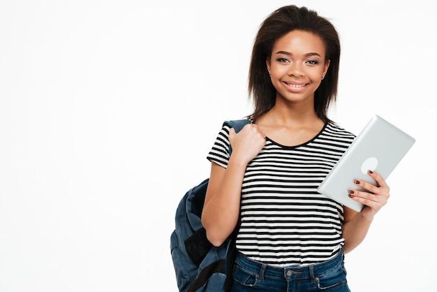 Glückliche lächelnde jugendlich frau mit rucksack, der pc-tablette hält