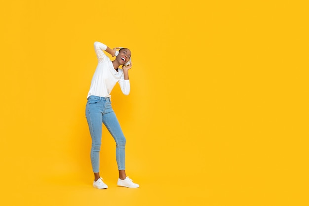 Glückliche lächelnde junge afroamerikanische frau, die musik auf kopfhörern lokalisiert hört