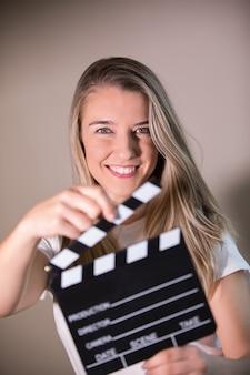Glückliche lächelnde junge blonde frau, die kinoklöppelbrett hält