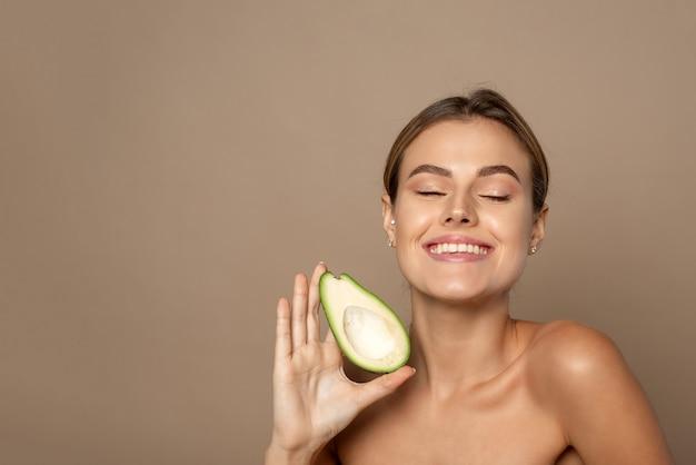 Glückliche lächelnde junge frau, die avocadohälfte auf einem beige hintergrund hält. konzept der natürlichen schönheit.