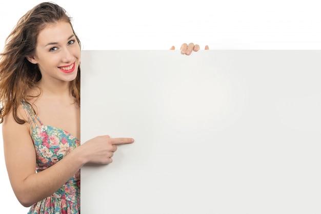 Glückliche lächelnde junge frau, die ein leeres leeres schild mit copyspace zeigt