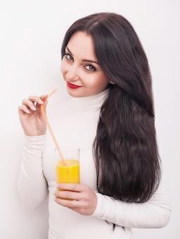 Glückliche lächelnde junge frau, die orangensaft trinkt