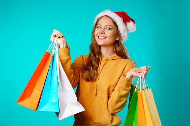 Glückliche lächelnde junge frau in der weihnachtsmütze, die einkaufstaschen hält