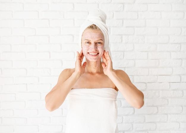 Glückliche lächelnde junge frau in weißen badetüchern, die peeling auf ihrem gesicht und hals anwenden