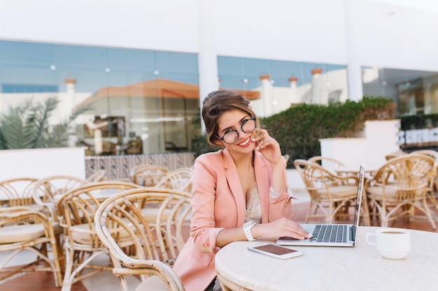 Glückliche, lächelnde junge frau mit laptop im straßencafé, die arbeit am computer draußen genießt, kaffee trinkend. tragen sie elegante kleidung - stilvolle rosa jacke, brille, weiße uhren.