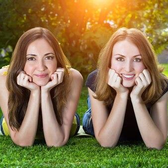 Glückliche lächelnde junge frauen, die auf gras liegen