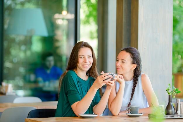 Glückliche lächelnde junge frauen mit kaffeetassen am café. kommunikations- und freundschaftskonzept