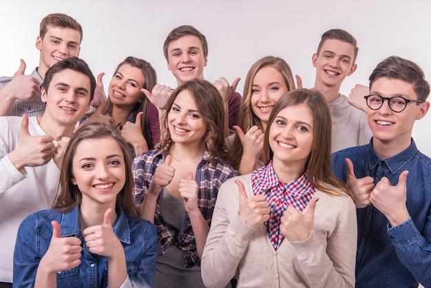 Glückliche lächelnde junge gruppe freunde mit den daumen oben.