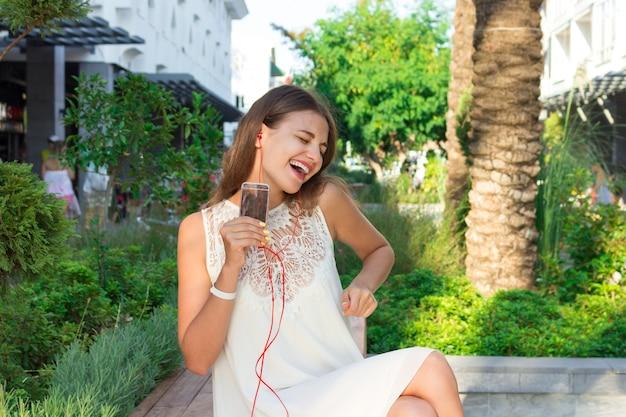 Glückliche lächelnde junge hübsche frau hört musik im kopfhörer und hat spaß