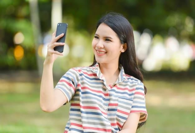 Glückliche lächelnde junge mädchen des frauentelefons, die selfie handykamera auf dem park nehmen selfie porträt mit smartphone-triebphotographie nehmen