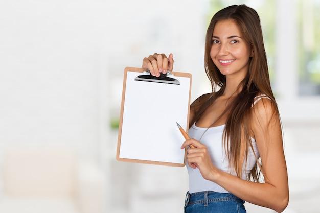 Glückliche lächelnde junge schöne geschäftsfrau mit zwischenablage