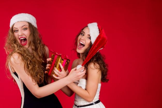 Glückliche lächelnde junge schönheitsfrau, die märchen santa christmas-hut wenig schwarzes weißes kleid feiert winterurlaub-parteispaßkampf des neuen jahres für das geschenk lokalisiert trägt