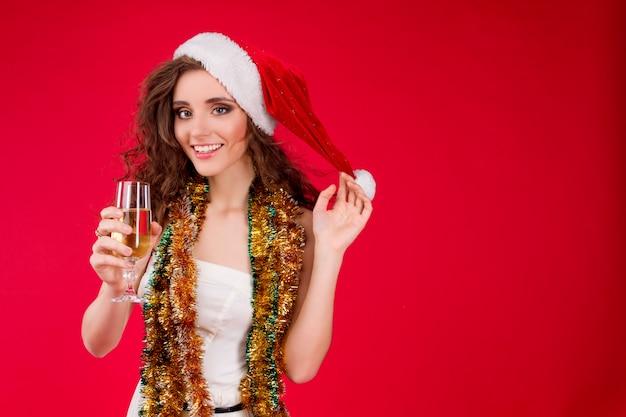 Glückliche lächelnde junge schönheitsfrau, die tragenden trinkenden champagner des feenhaften santa claus christmas-hutes wenig weißen kleiderlamettas feiert winterurlaube neues jahr kleidet