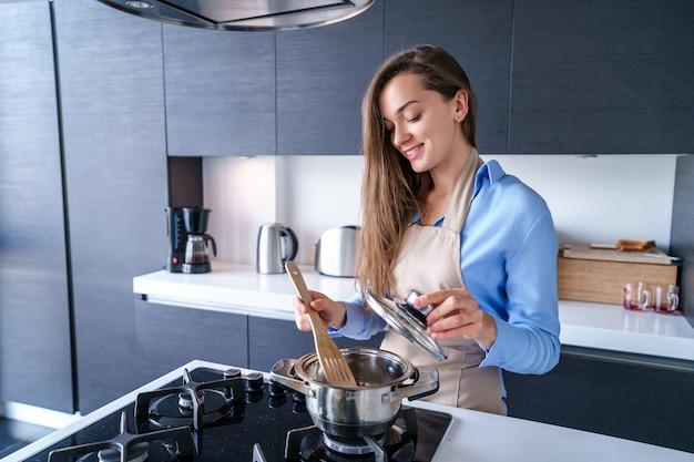 Glückliche lächelnde kochende hausfrau der frau in der schürze unter verwendung des stahlmetalltopfs für die zubereitung gekochter gerichte zum abendessen in der küche zu hause. küchenutensilien zum kochen