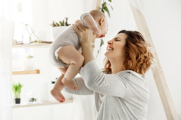 Glückliche lächelnde mutter, die mit neugeborenem kind im bequemen hellen schlafzimmer vor fenster spielt. momente des mutterschaftsglücks mit kindern. familienkonzept.