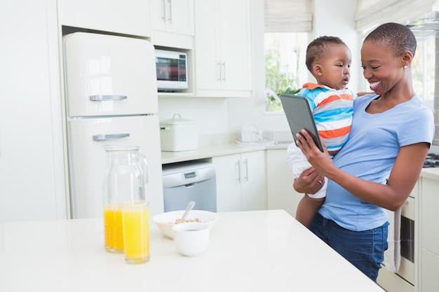 Glückliche lächelnde mutter mit hisbabyboy, das digitale tablette verwendet