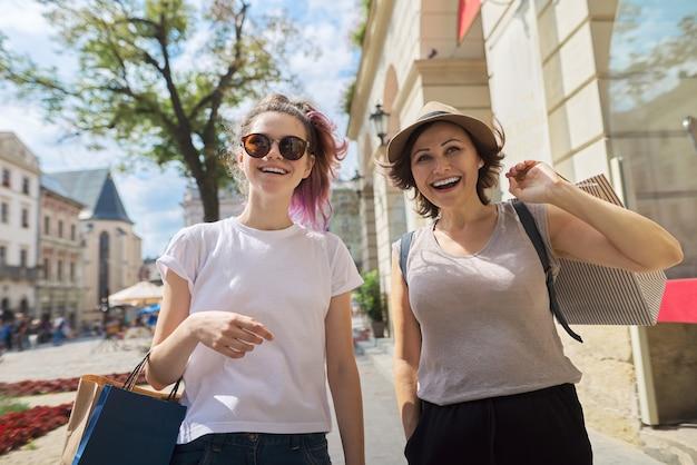 Glückliche lächelnde mutter und jugendliche tochter, die zusammen mit einkaufstüten gehen.