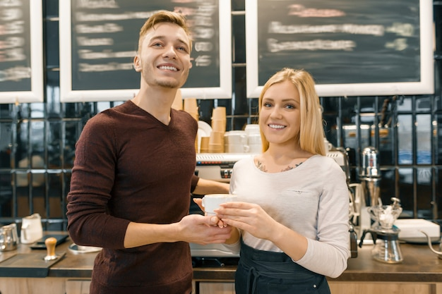 Glückliche lächelnde paare am kaffeestubenzähler