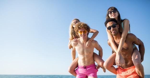 Glückliche lächelnde paare, die am sonnigen strand spielen