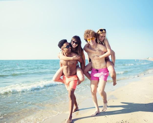 Glückliche lächelnde paare, die am strand spielen