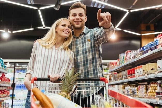 Glückliche lächelnde paare mit einem laufkatzeneinkaufen