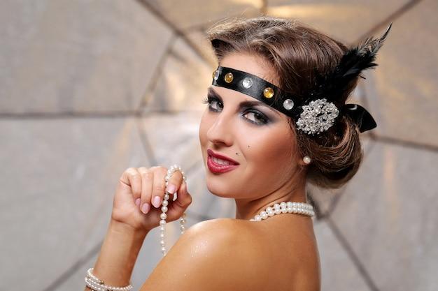Glückliche lächelnde partyfrau und hand der perle