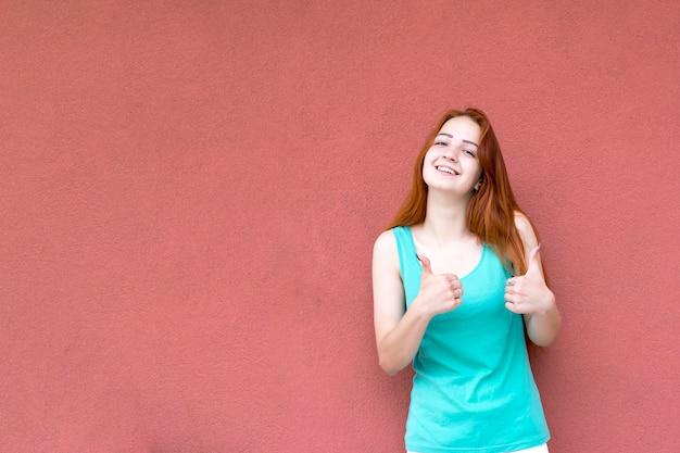 Glückliche lächelnde rothaarige frau, die sich daumen zeigt