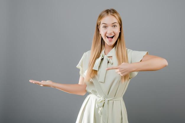 Glückliche lächelnde schöne blonde junge frau, die finger auf das copyspace lokalisiert über grau zeigt