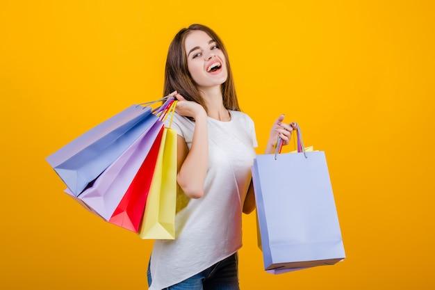 Glückliche lächelnde schöne brunettefrau mit den bunten papiereinkaufstaschen, welche die jeans und hemd lokalisiert über gelb tragen