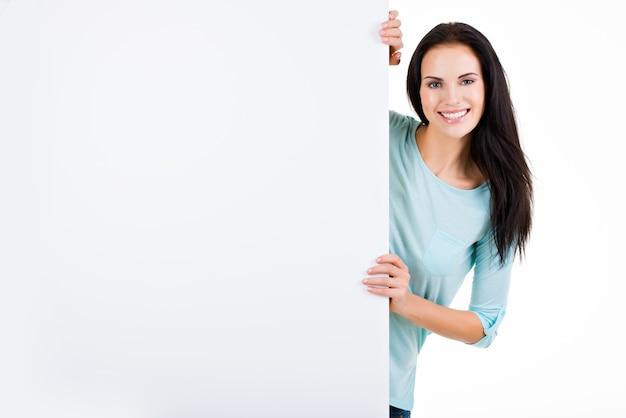 Glückliche lächelnde schöne junge frau, die leeres schild lokalisiert auf weiß zeigt