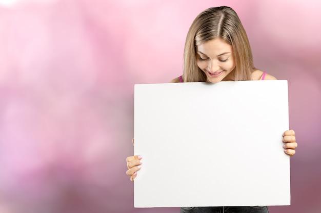 Glückliche lächelnde schöne junge frau in der rosa intelligenten freizeitbekleidung, die leeres schild oder copyspace für slogan oder text zeigt