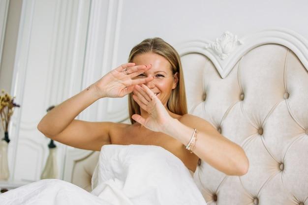 Glückliche lächelnde schöne lange angemessene haarfrau im schließend gesicht der unterwäsche, das auf bett im hellen reichen innenraum sitzt