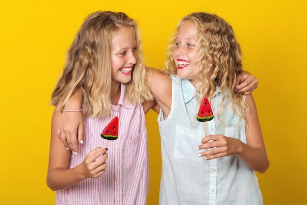 Glückliche lächelnde umarmende und laughingle zwillingsschwestern