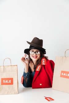 Glückliche lächelnde verkaufsfrau, die mit papiereinkaufstüten sitzt