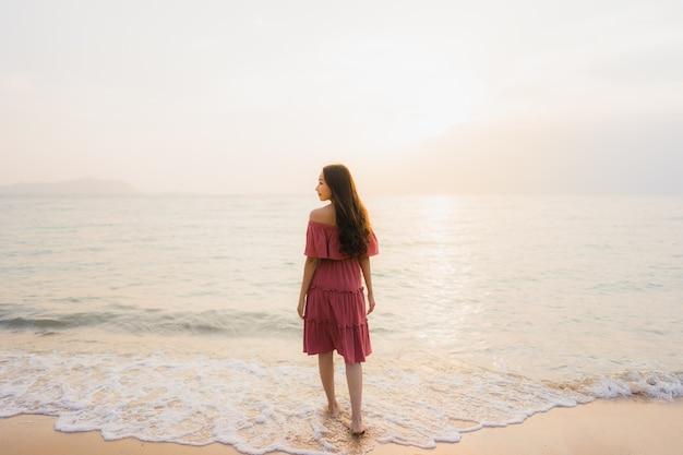 Glückliche lächelnfreizeit der schönen jungen asiatischen frau des porträts auf dem strandmeer und -ozean